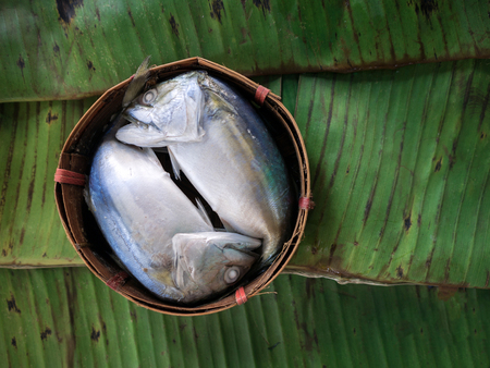 Steamed mackerel in the basket of bamboo ,banana leaves background