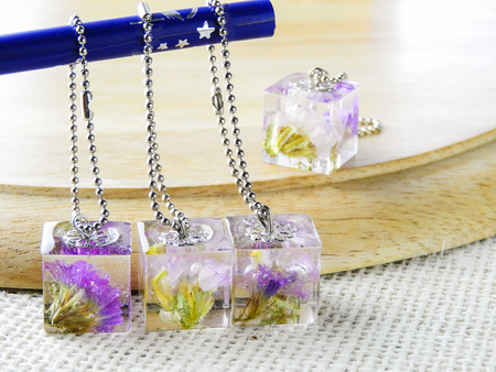 Dried flower in crystal clear resin pendant necklace, pendant with a real flowers. 免版税图像