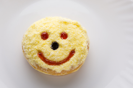 Smiley donut on a white plate, donut with white background