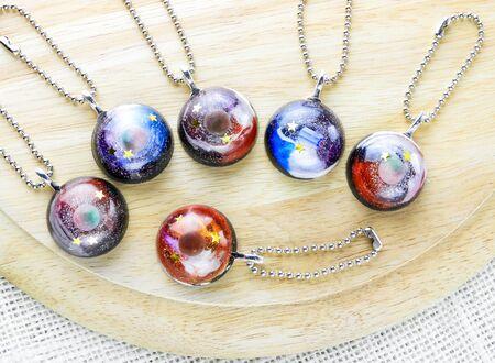 Crea posavasos con forma de galaxia usando resina, purpurina y pigmentos en polvo, artículos hechos a mano. Apto para llaveros, collares y colgantes. Foto de archivo