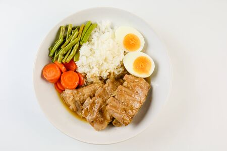 Baked pork ribs with rice, boiled egg and vegetable Stockfoto