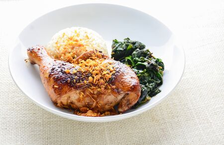 Chicken drumstick marinated with spicy chilli sauce and herbs, served with cooked rice and spinash. Stock Photo - 128850263