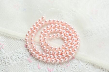 pearl necklace on white fabric background, Close up shot of glass pearls Imagens - 129684613