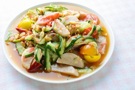 Cucumber salad with preserved pork sausages, Thai popular food called Som Tum Tang, Hot and spicy, mixed vegetables.
