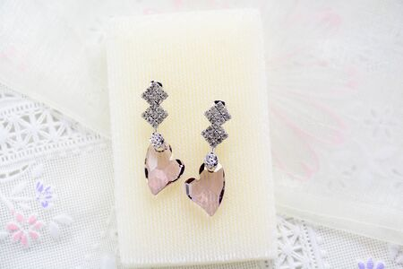 Crystal earrings on white fabric background