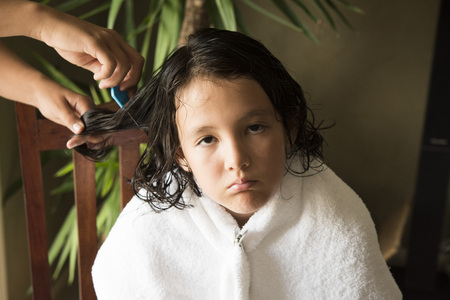 a girl is upset face, she is doing head lice treatment