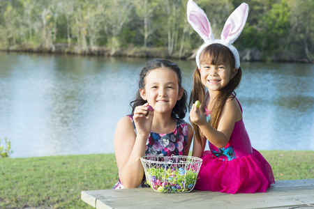 rabit: the happy sisters are eating easter chocolates at outside Stock Photo