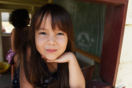 kindy: a girl is smiling from cubby house window. Stock Photo