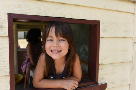 cubby: a girl is smiling from cubby house window. Stock Photo