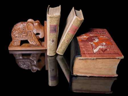 Three old books and support a wooden elephant are on a black mirror Stock Photo