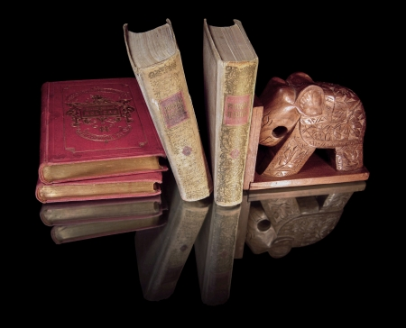 Four old books and support a wooden elephant are on a black mirror