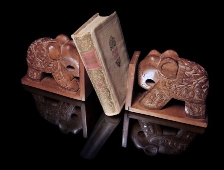 Two wooden elephants and one book are on a black mirror Stock Photo - 14314302