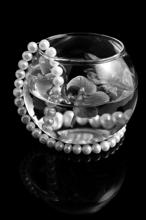 It is the black-and-white photo of an orchid in a glass vase with pearls Stock Photo