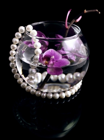 The branch of an orchid and pearls is in a glass vase