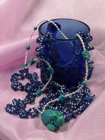 On a pink background there is a dark blue glass cup in which there are necklaces from beads, pearls and a turquoise stone