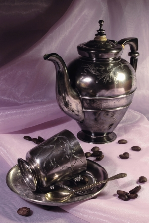 Silver coffee service of the 19th eyelid, coffee pot and cup and coffee grains located on pink silk