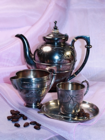 Silver coffee service of the 19th eyelid, coffee pot, milk jug and cup and coffee grains located on lilac silk