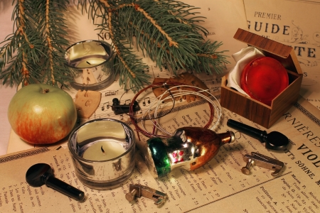 The still life from a branch of a fir-tree, violin strings, kolok, supports, candles, boxes with rosin, a glass lodge and apple lies on old reports musical parts photo