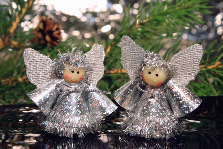 Two angels are on a mirror against from fir-tree branches Stock Photo