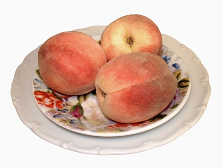 Three juicy peaches on a  saucer and a white plate
