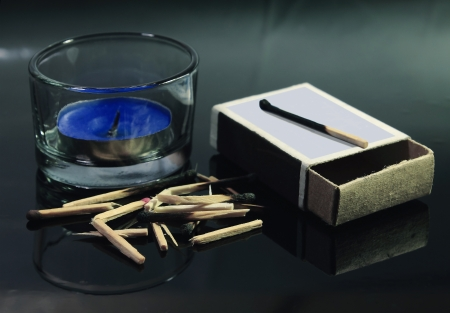 On a black mirror are an extinct candle, empty match boxes and a hill of the broken matches