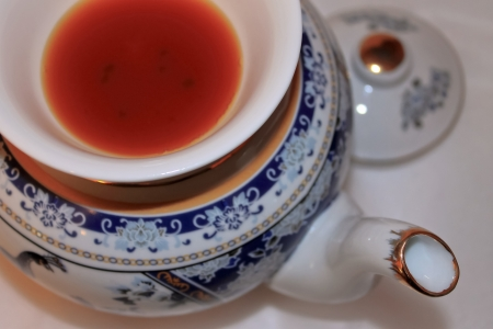 The image of a porcelain teapot and Asian drinking bowl with red tea, macro, the top view