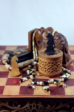 On a chessboard there is an elephant from a wood, a casket from birch bark and a wood, a beads from an ivory and handmade chessman