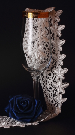 Blue  silk rose,tall glass with gold and white laces on a black background