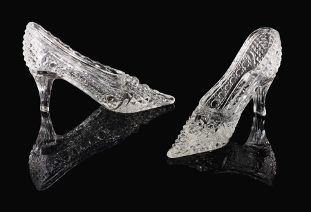 Two crystal shoes of the Cinderella stand on a black mirror Stock Photo