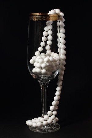 Glass and white necklace on a black background Stock Photo