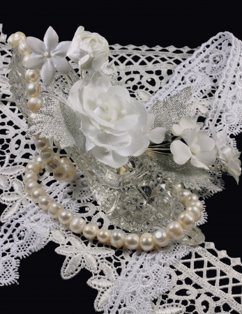 Group of jewelry for the bride with a crystal shoe and a necklace from pearls on a black background  photo
