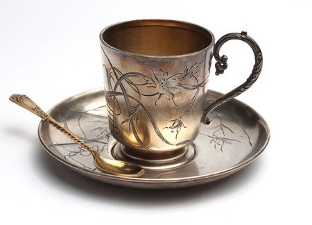 Antiquarian silver cup with a saucer and a spoon on a white background