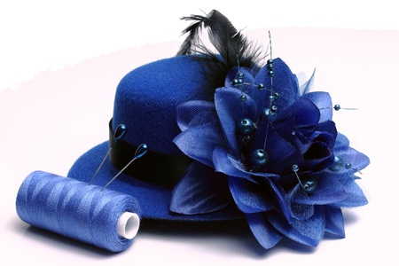 Blue hat with a feather and a flower, the coil of blue threads and two pins on a white background