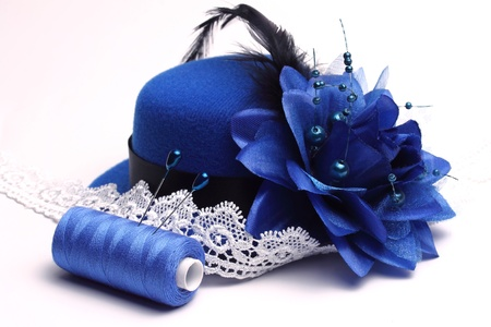 Blue hat with a feather and a flower and a the White lacy ribbon on a white background Stock Photo