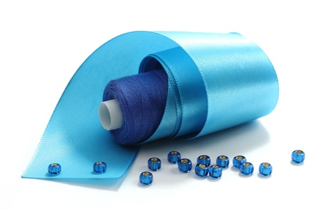 Blue tape, the coil of blue threads and blue beads on a white background Stock Photo