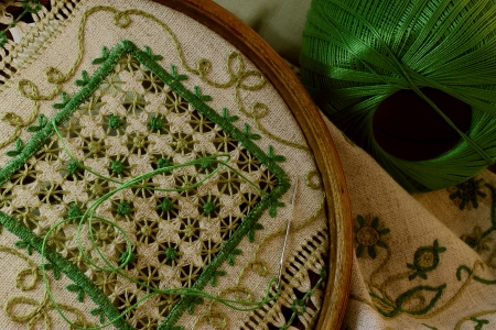 Pattern embroidered with green threads on rough linen fabric, an antiquarian, round, wooden frame, a hank of green threads, a needle.