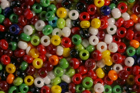 Very bright, brilliant, multi-  colored beads are photographed   very largely