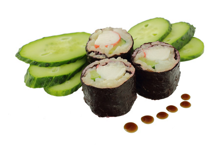 Three sushis with a crab and a cucumber, slices of a cucumber and drops of soy sauce on a white background