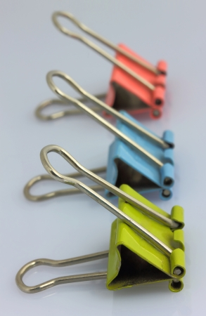 Three color clips for papers are on a gray table