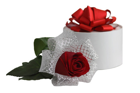The image of a white round gift box with a red tape and red rose with a silver tape is on a white