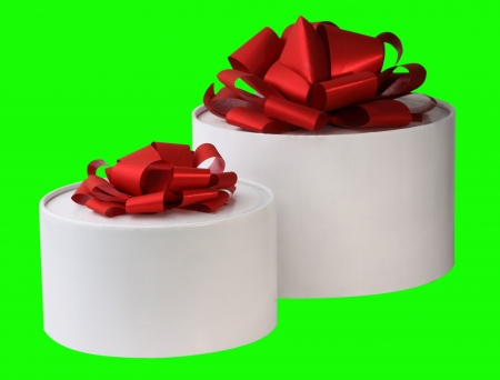 The image of two white gift round boxes with red tapes is on a green  Stock Photo