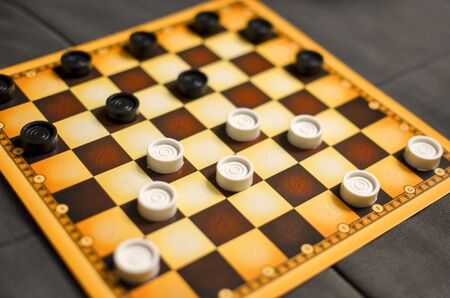 Checkerboard with checkers. Business strategy competition, strategic planning for winning success. Hobby. checkers on the playing field for a game. Standard-Bild
