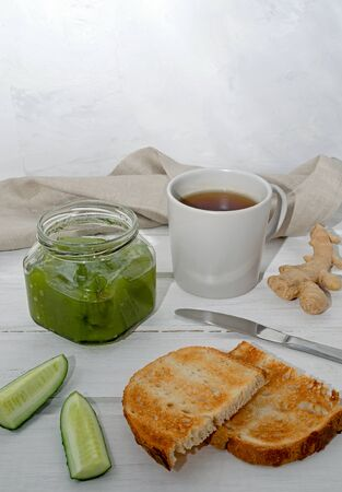 green cucumber jam in a transparent jar with slices of cucumber and ginger with toast, a knife and a textile napkin on a light wooden background. Healthy eating concept. flexitarian. keto diet. Stock Photo