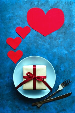 festive concept. gift in craft eco paper with red ribbon on blue plate with fork and knife on blue background with hearts. romantic composition. birthday, valentines day or other universal greetings Stock Photo - 137485540