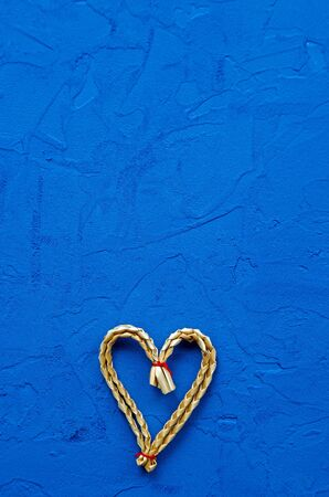 zero waste concept. eco-friendly wicker straw heart on a blue background. Congratulations on Valentine's Day, birthday or other holiday. vertical orientation blank for postcards