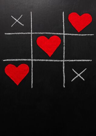 lovers day concept. tic-tac-toe game where instead of zeroes are red hearts. on a black background. vertical orientation Stok Fotoğraf
