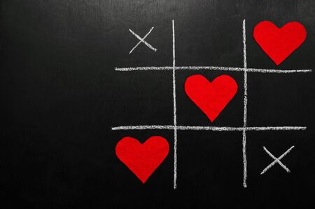 lovers day concept. tic-tac-toe game where instead of zeroes are red hearts. on a black background. horizontal orientation with copy space.