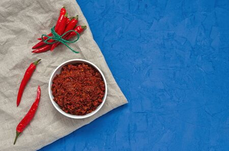 Hot chilli pepper sauce paste harissa, traditional Tunisia, Moroccan, Arabic cuisine adjika ,chili spices and fresh red chilli peppers, over blue background. Zdjęcie Seryjne