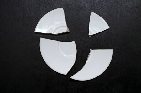 four-piece white plate on a black background. concept of broken heart, broken life. close-up