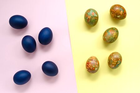 Easter holiday concept. classic blue eggs on a pink background against bright multi-colored trendy trendy marble eggs on a yellow background. copy space